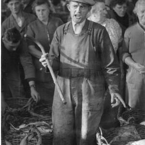239 - Baskets of fish surrounding man with stick in his hand