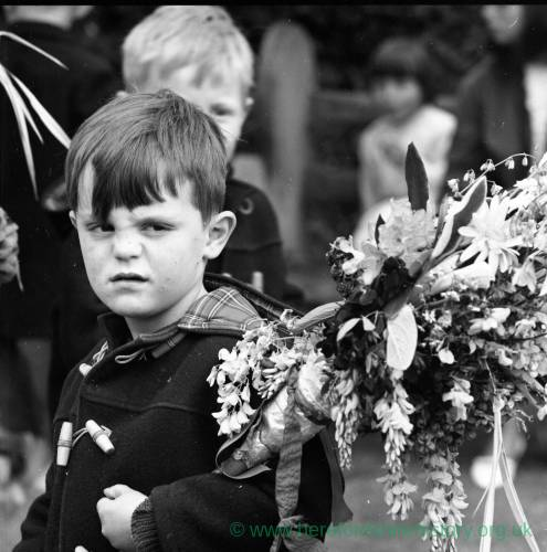 Young boy carrying decorated floral stick at the Heart of Oak Club Walk, May 1965
