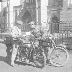 Two men on motorbikes outside Hereford cathedral.