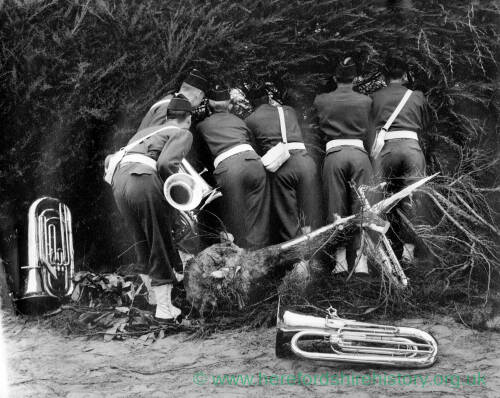 186 - Six army band members peering through the hedge