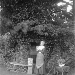 G36-225-01 Lady, standing holding a kitten, in garden beside ivy-covered tree.jpg