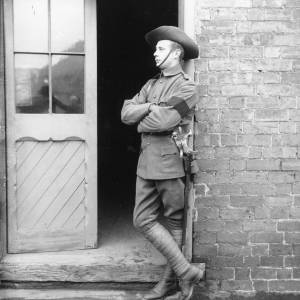 G36-039-02 Full length portrait of man in uniform with sword and black armband.jpg