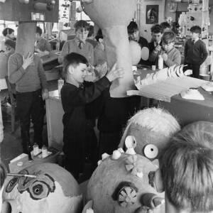 Schoolboys making large papier mache heads.