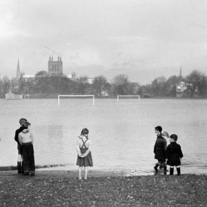 Group of children at the edge of flooded playing field 2