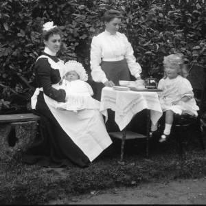 G36-029-04 Tea being served in garden to little girl. Nurse with baby.jpg