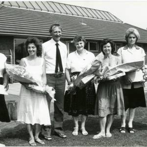 RG1888 Six women and a man holidng flower bouquets and gifts, 21st July 1983.jpg