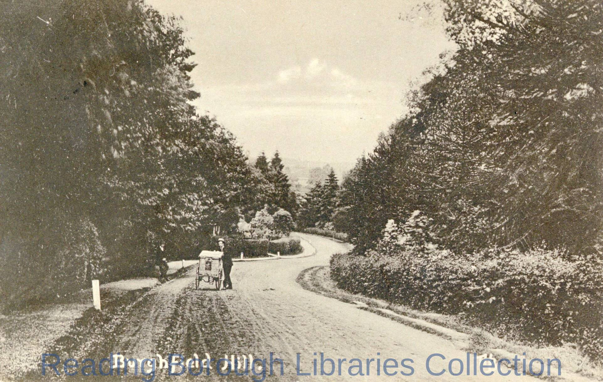 A man pushing a handcart, which carries a large wicker hamper up the hill towards the camera, Burghfield Hill, c1910