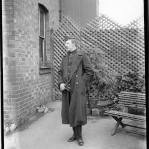 G36-034-04 Man in uniform; greatcoat and swagger cane, forage cap. In yard of house, pointed trellis and seat behind .jpg