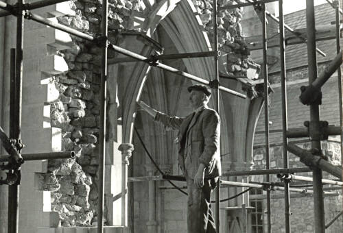Master Mason George Down examining bomb damage to St James' Chapel, Exeter Cathedral
