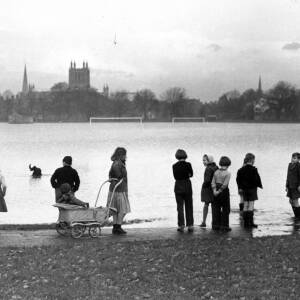 Children standing near floodwater at Bishops Meadows, Hereford.