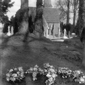 G36-211-07 New grave with five wreathes at Hereford Cemetery, with the chapel in the background.jpg