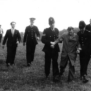 A suspect is escorted across fields by policemen.