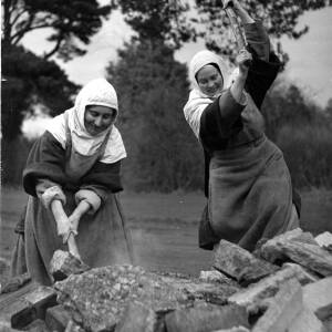 Two nuns breaking up concrete for the chapel foundations.