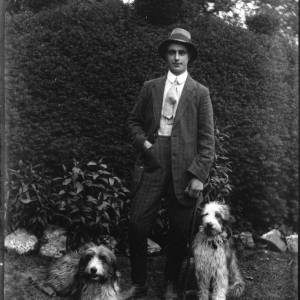 G36-296-03 Young man and 2 dogs in garden.jpg