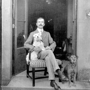 G36-330-18 Man seated in doorway with two dogs.jpg