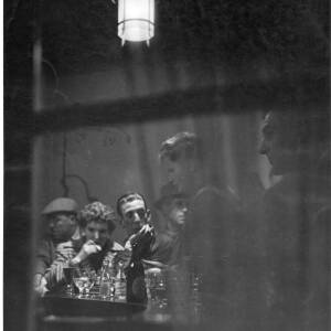 275 - Looking inside bar; several men and one woman inside