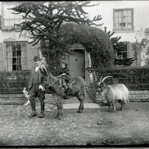 G36-020-01 Girl on donkey held by man with dog and goat behind, in front of a clipped arch and house.jpg