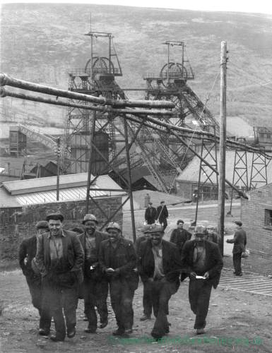 Group of miners leaving work with the colliery in background