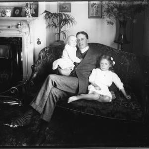 G36-033-04 Interior. One man sitting on a settee with girl and baby.jpg