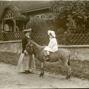 G36-009-07 Girl on donkey with mother outside house.jpg