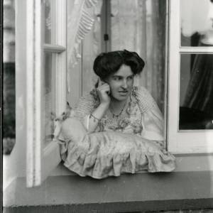 G36-009-01 Lady leaning on a cushion looking out of window.jpg