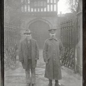 G36-102-11 Older bearded man with son in  Army uniform at Bishop's Palace gates jpg.