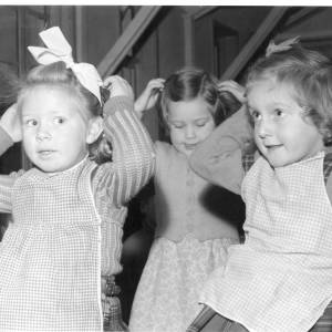 Three small children performing in a play.