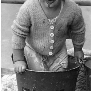 A young boy having fun in a fire bucket!