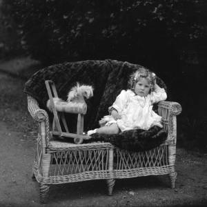 G36-029-03 Child from family group on wicker sofa with wheeled wooden pusher horse .jpg