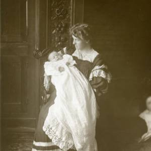 G36-009-12 Lady holding baby in christening robe indoors.jpg