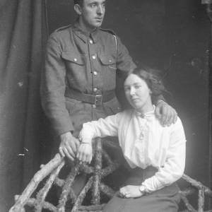 Soldier stood with lady sat on bench