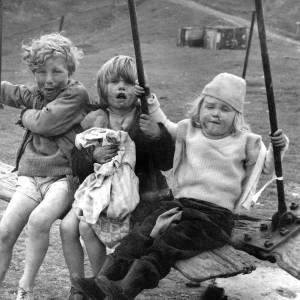 Three children on a swing.