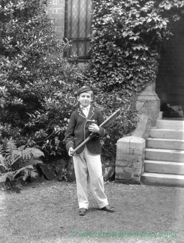 G36-221-07 Boy with cricket bat, wearing school blazer, cap and long trousers, outside large house [as G36-221-01].jpg