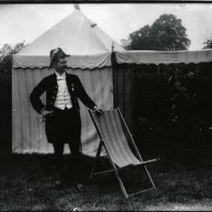 G36-012-05 Man in apparent court dress outside tent in garden.jpg