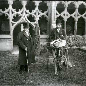 G36-194-07 Two men, one on tricycle by cloisters.jpg