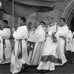 Choristers hold a canopy over a priest.