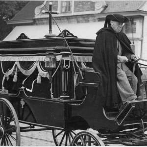491 - Man with black cloak & hat driving hearse carriage