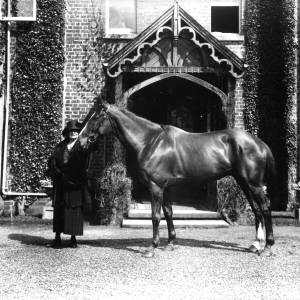 G36-541-02 Lady in hat and coat holding halter of a horse, at door of house.jpg