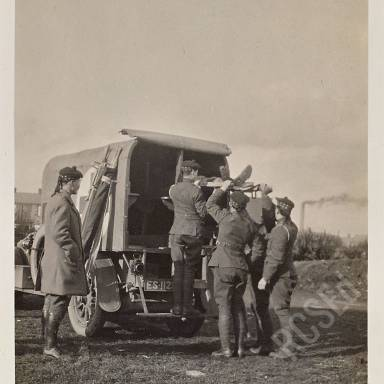 Loading wounded into motor ambulance under direction of Corporal Buchanan
