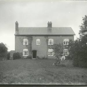 G36-019-06 Man seated with dog and lady standing in garden in front of house.jpg