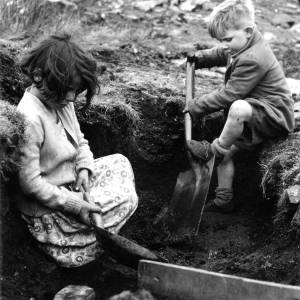 Young boy and girl digging on a slag heap.