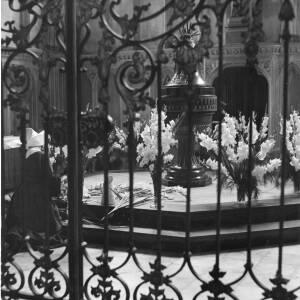 261 - Nun arranging flowers in church; picture taken outside railings