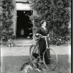 G36-018-02 Lady with bicycle and long-haired dog outside open door.jpg
