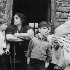 Welsh women and children outside a stone house.