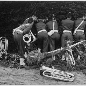 633 - Six army band members peering through hedge