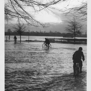 479 - Three cyclists riding through flood at Bishops Meadow