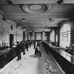 Photograph showing busy customer counters in the main hall of Crédit Commercial de France's head office at 103, avenue des Champs-Elysées