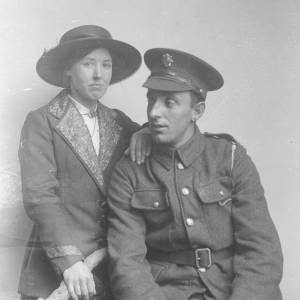 Lady in hat stood with hand on the shoulder of a sitting soldier in uniform