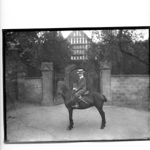 G36-331-06 Lad wearing a straw boater and a suit with an Eton collar, seated on a pony in front of the Bishop's Palace gates.jpg