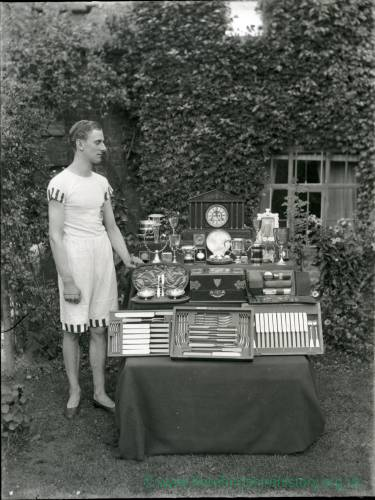 G36-216-03 Young man in garden with trophies .jpg